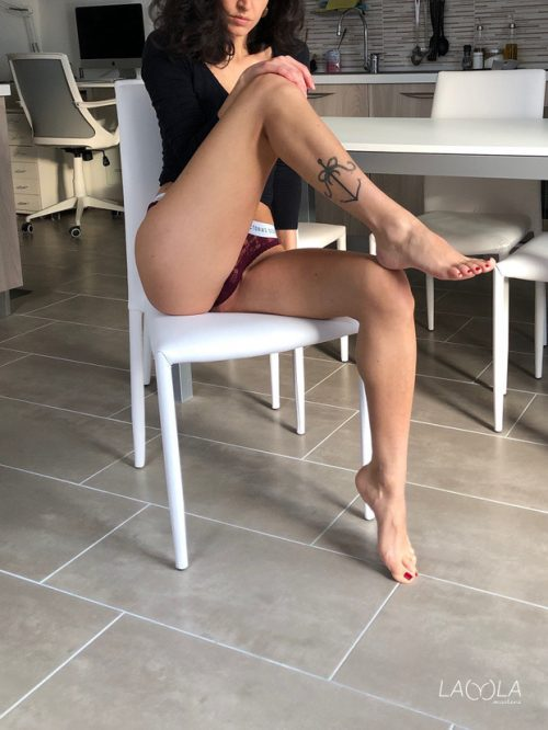 On the chair wearing a thong